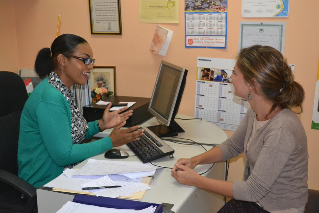 In a small office, a student doing a Psychology internship abroad has a friendly chat with a member of staff in Jamaica.